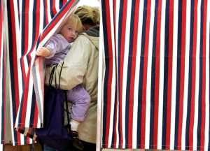 Elyse Holmes, 2, peaks out as her mother Helen Holmes votes at Madbury Town Hall in Madbury